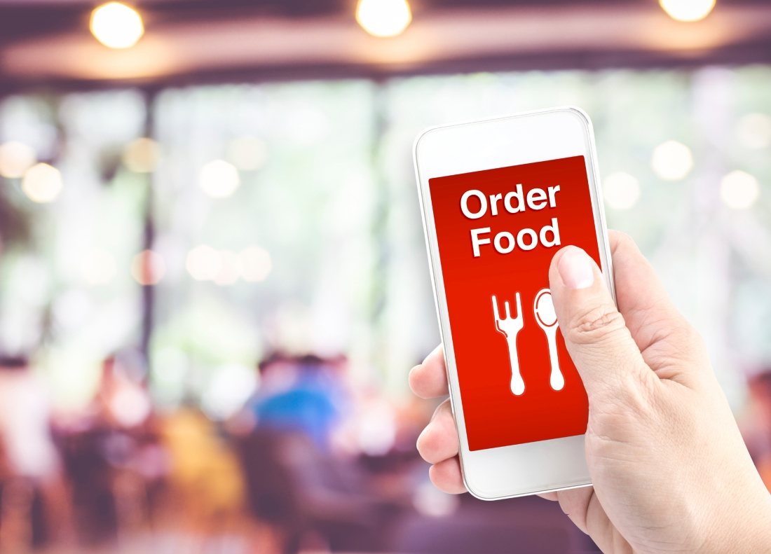 Hand holding mobile with Order food with blur restaurant backgro
